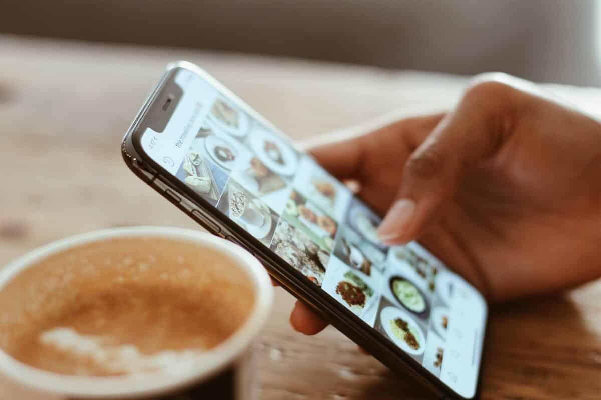 quelqu'un regarde des photos instagram sur son téléphone portable en train de boire du café